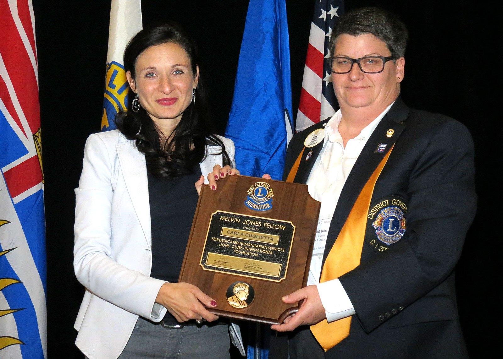Carla Cuglietta is presented the award for 2017's Citizen of Distinction by DG Kris Kozoriz